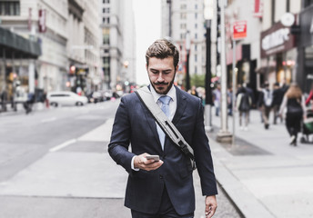 Businessman walking with cell phone in Manhattan, New York City, USA