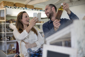 Happy couple taking pictures with smartphone in farm shop