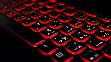 Close up. Red backlight, backlit on laptop computer or keyborad computer of gaming in the dark. Concept Thai computer keyboard background.