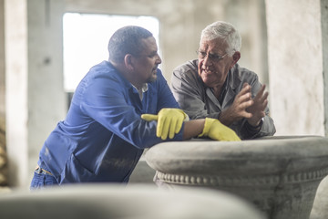 Two men talking in industrial pot factory