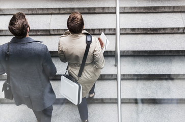 Businessman and woman walking on stairs