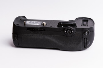Battery grip for DSLR cameras isolated on white background.