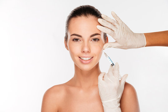 Young woman gets beauty injection in eye area from sergeant