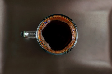 cup of black coffee on a brown plate