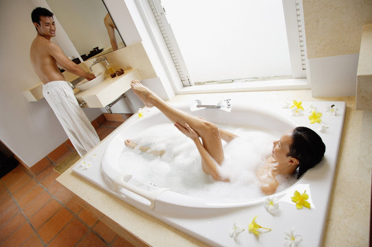 Couple in bathroom, woman taking at bath, washing leg, man standing at sink