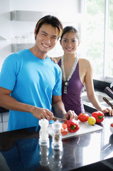Couple standing in kitchen, looking at camera, man holding knife, chopping vegetables