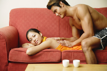 Woman lying on sofa, man giving her massage