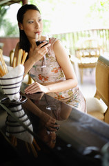 Woman sitting at bar counter, drinking wine