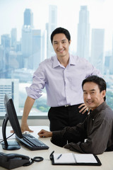 Male executives in office, smiling at camera