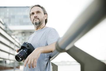 Fotograf mit einer Kamera in der Hand, Spiegelreflexkamera,  schaut nachdenklich