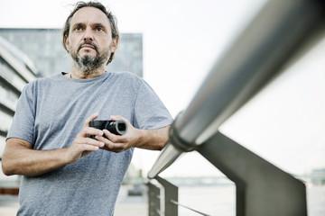 Mann steht an einem Geländer mit einer digitalen Kompaktkamera in der Hand, Portrait,