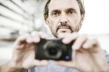 Mann fotografiert mit seiner digitalen Kompaktkamera