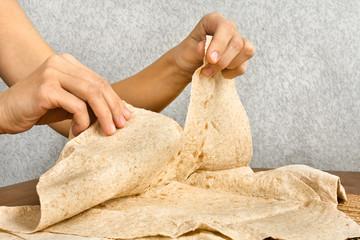 hands tear off a piece of pita bread, closeup