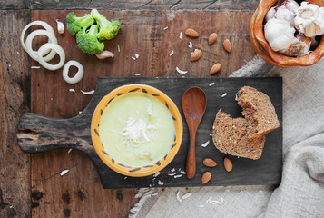 Broccoli  cream soup and brown bread on the black wooden board.