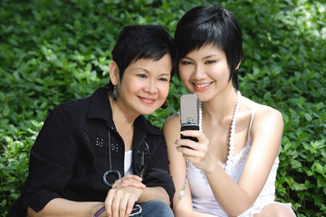 Women side by side, smiling, looking at mobile phone