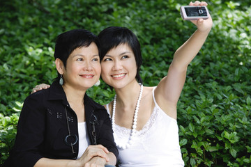 Women side by side, smiling, taking a picture with mobile phone