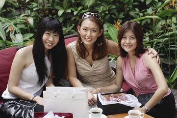 Three women at outdoor garden cafe, sitting side by side, smiling at camera