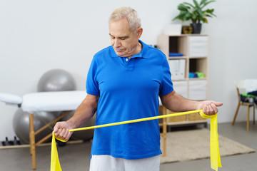 senior trainiert in einer praxis mit einem gymnastikband