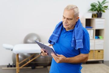 älterer mann mit einer checkliste für sein physio-programm
