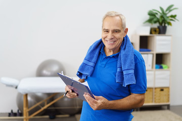 älterer mann mit einer checkliste für sein physio-training
