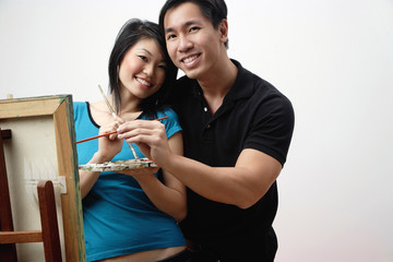 Couple at home, standing in front of easel with palette and paint brushes