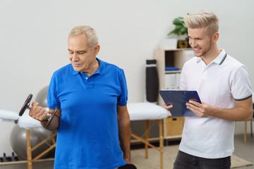 senior trainiert mit hanteln mit einem physiotherapeut