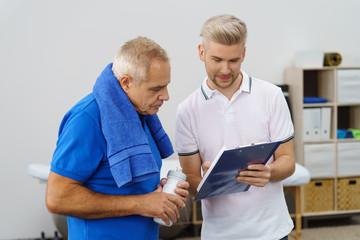 therapeut berät einen älteren mann bei der physiotherapie