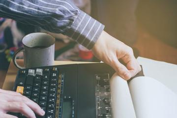 Escritor joven preparándose para trabajar con una taza de café sobre su mesa