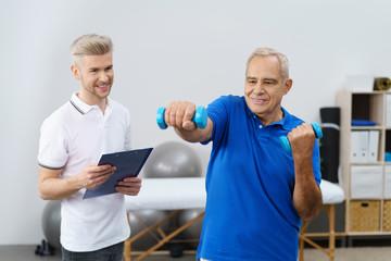 senior trainiert mit kleinen hanteln in der physiotherapie