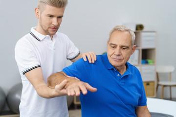 physiotherapeut untersucht die schulter eines älteren patienten