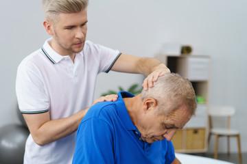 senior mit nackenschmerzen in der behandlung beim physiotherapeuten