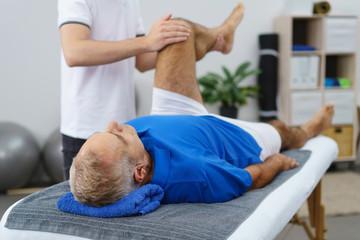 senior lässt sein knie beim therapeuten behandeln