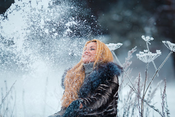 beautiful woman with long red hair on a snowy Cow Parsnip throwing snow up selective focus