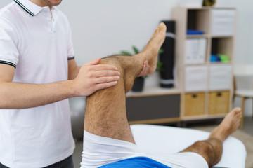 physiotherapeut untersucht das knie eines mannes in der praxis