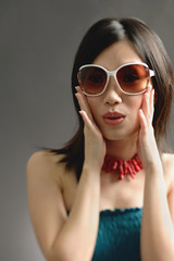 Woman wearing large sunglasses, hands on face