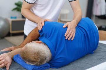 physiotherapeut behandelt einen älteren mann an der schulter