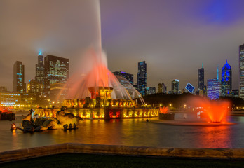 Papiers peints Chicago Chicago skyline panorama with skyscrapers and Buckingham fountain in Grant Park at night lit by colorful lights.