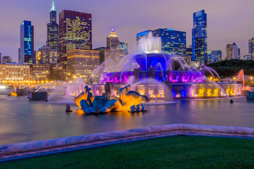Papiers peints Fontaine Chicago skyline panorama with skyscrapers and Buckingham fountain in Grant Park at night lit by colorful lights.