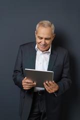 älterer unternehmer schaut auf sein tablet