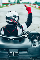 Carting Woman driving go-cart. Finger up after won race