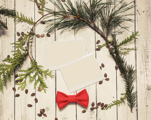 Photo frame stick on vintage wooden texture. Christmas and New Year background concept. Polaroid frames on retro style table. spruce branches and red bowtie