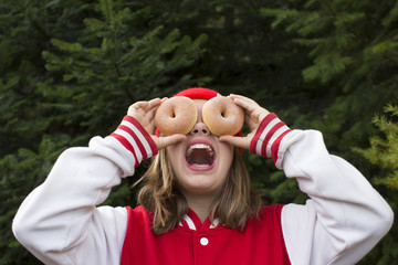 A teenage girl being silly holding two donuts over her eyes in Sagle, Idaho.