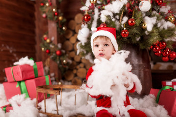 Little child (boy) in the costume of Santa Claus played with white snow near the Christmas tree with gifts