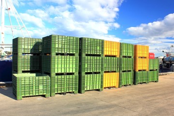Green and yellow fishing containers stacked on wharf or jetty