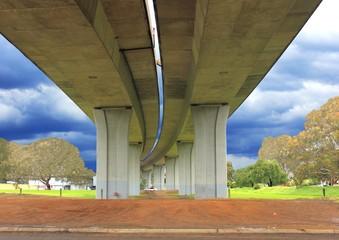 Underneath concrete road bridge with storm clouds on horizon