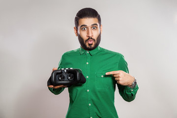 Young emotional middle eastern excited man with beard and green shirt using a VR headset and experiencing virtual reality.