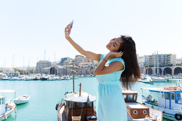 Lovely happy smiling tourist girl taking self-portrait picture u