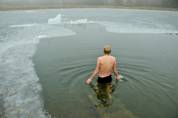 Man swimming in the ice during cold winter day