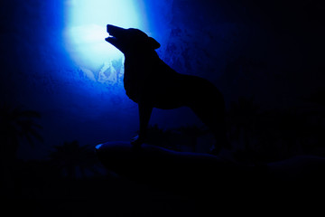 wolf in silhouette howling to the full moon