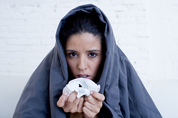 young attractive hispanic woman lying sick at home couch in cold and flu  in gripe disease symptom